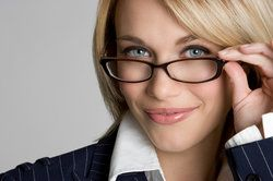Attractive blond businesswoman peering over rim of her glasses