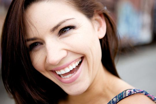 Laughing brunette woman squinting eyes