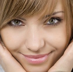 Smiling woman with flawless skin holding chin in hands