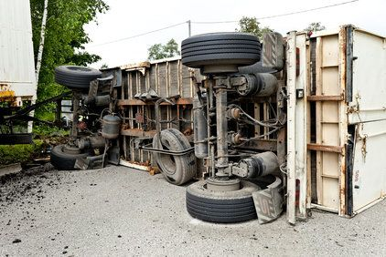 View of undercarriage of a fallen big rig truck laying on its side