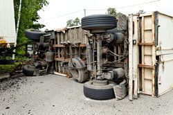 An overturned truck after a serious accident, possibly caused by driver fatigue
