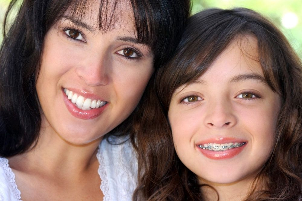 A young girl and her mother smile happily and peacefully.