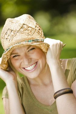 A girl wearing a woven hat holds it tightly down on her head while smiling and laughing.