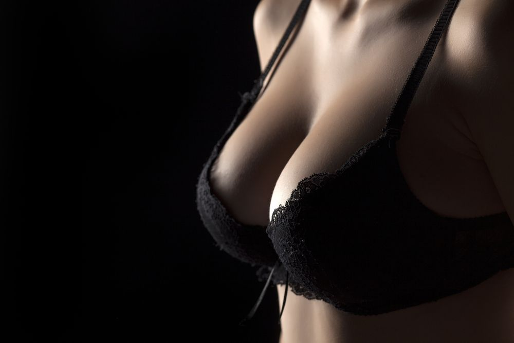 A photo of a woman wearing a black lace bra