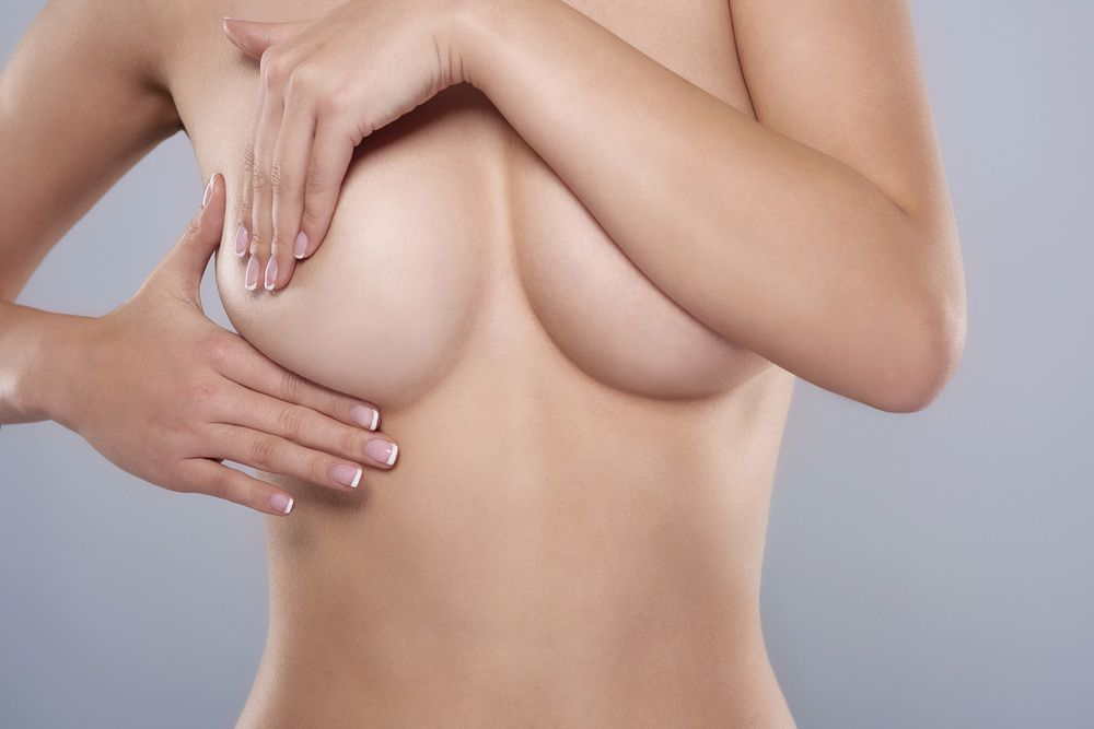 A topless woman covering her breasts