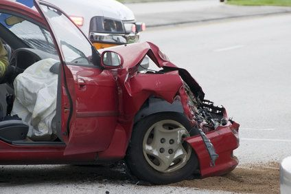 A smashed red car that has been in an accident.