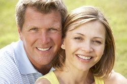 Middle-aged man and woman smiling, showing off their healthy teeth