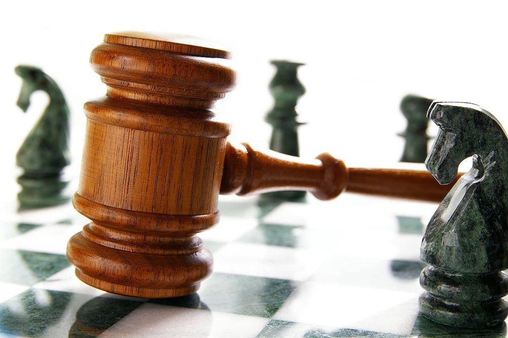 A judge's gavel resting on a chess board