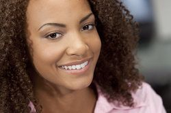 Smiling woman with curly brown hair and white teeth.