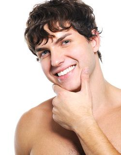 A shirtless young man holding his chin and smiling, showing off his perfect bite after orthodontic treatment