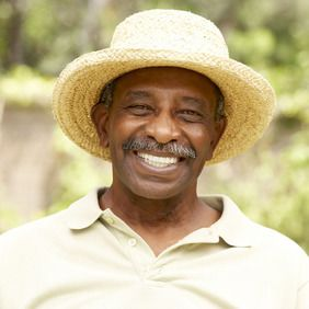An elderly man with a mustache wearing a straw hat