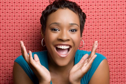 Attractive African American woman holding hands in front of mouth in exclamation
