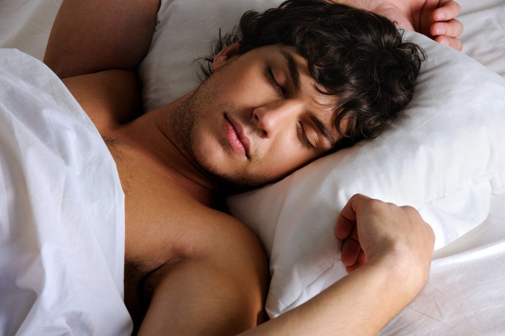 Man sleeping peacefully in white bedding