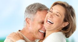 Middle-aged couple laughing and man nuzzling woman's neck