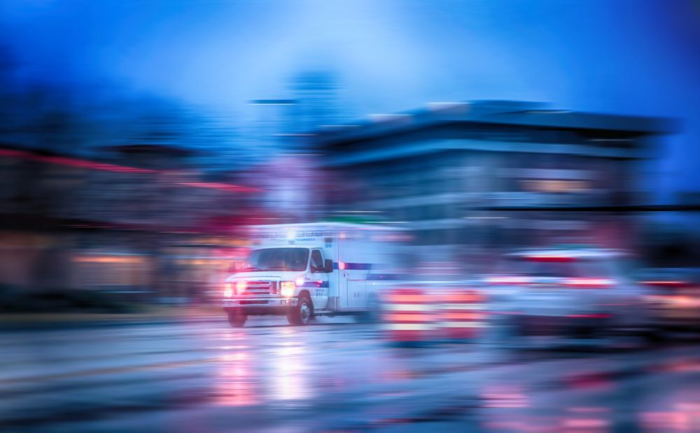 A blurred photo of a road with an ambulance