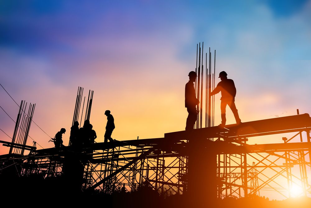 Silhouettes of steel workers working on the construction of a building at sunset