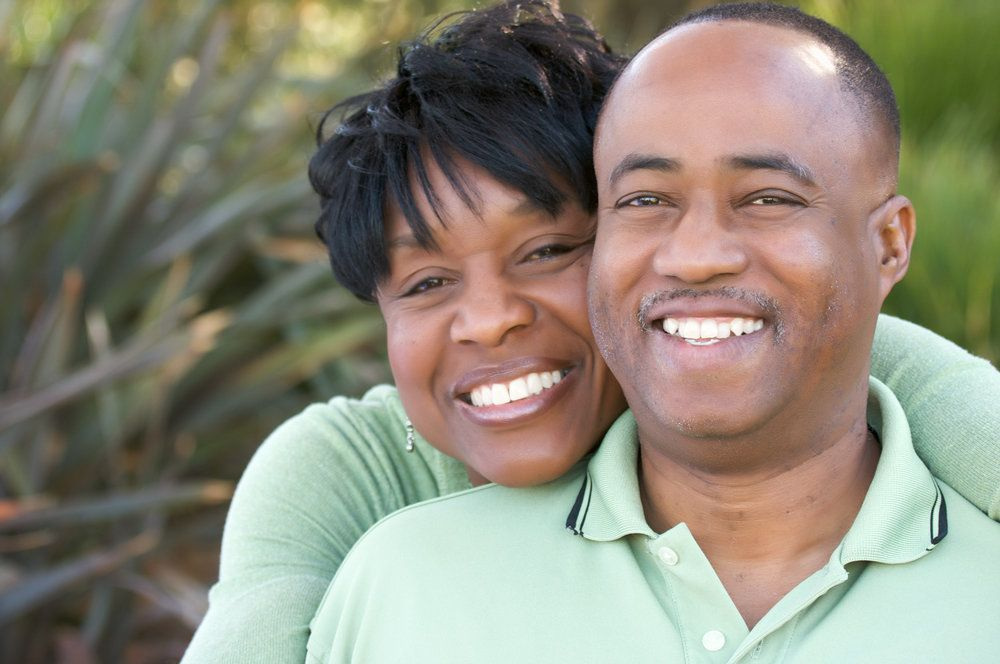 Attractive and affectionate African-American couple posing in the park