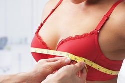 A woman's breasts being examined and measured