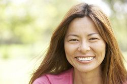 A middle-aged woman smiling, showing off her beautiful implant-supported dental bridge