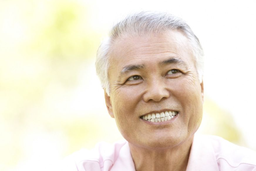 An older man shares a healthy smile