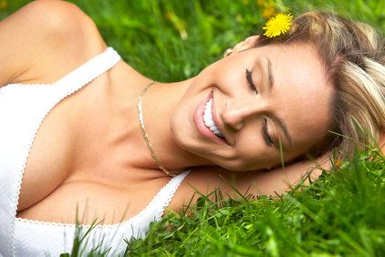 Laughing woman with full cleavage in white tank top lying on side in grass