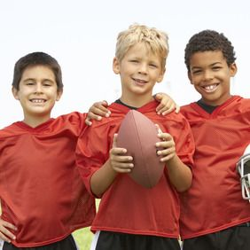 Three young boys in football jerseys pose for the camera