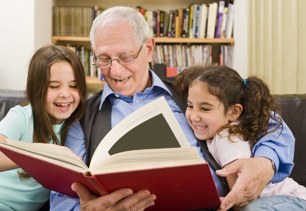 A grandpa reading to his granddaughters