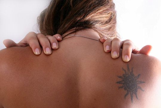 A woman's back with a tattoo on her right shoulder