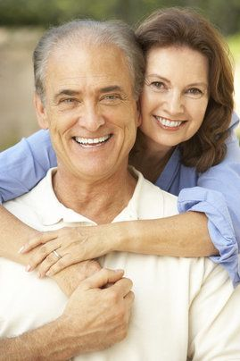 An older couple embracing and smiling outside