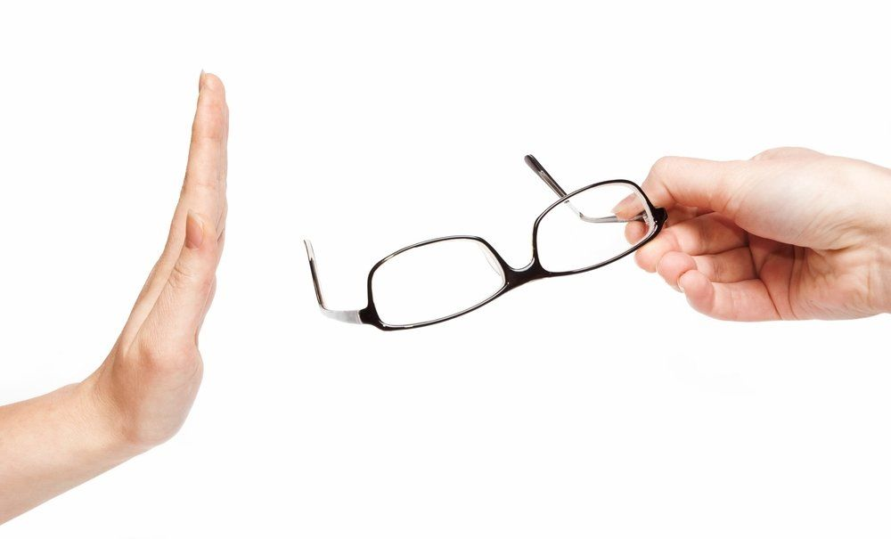 A hand rejects a pair of glasses being offered by another hand.