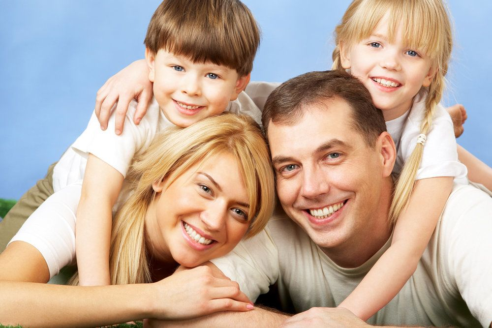 Smiling couple with two children draped on their backs