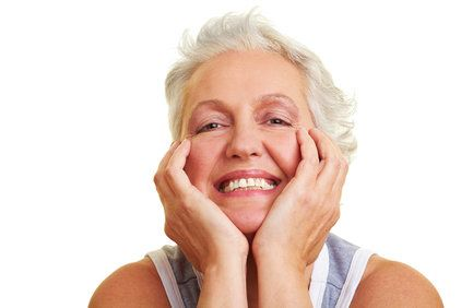 Smiling elderly woman resting chin in hands