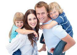 Smiling family enjoying piggyback ride against a white background