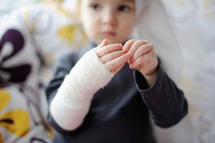 Sad-looking child with bandaged arm