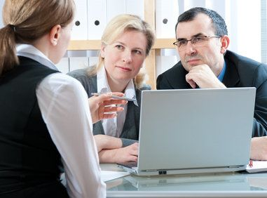 Woman speaking with businessman and businesswoman sitting in front of laptop