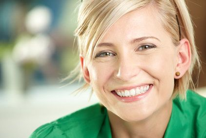 Smiling blond woman in green shirt