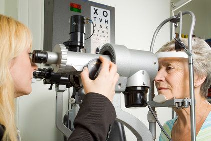 An elderly lady is examined by an eye care technician.