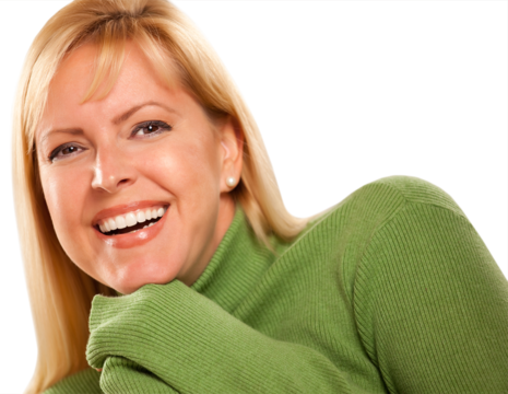 Smiling blond woman with hands wrapped in green turtleneck sweater
