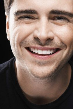 A man smiling happily, his healthy gums perfectly proportionate to his teeth