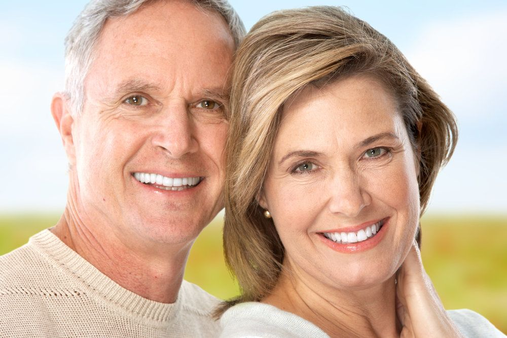 A couple smiles after their periodontal treatment