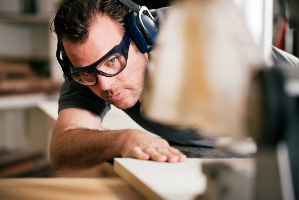 A man wearing safety glasses working with a planer