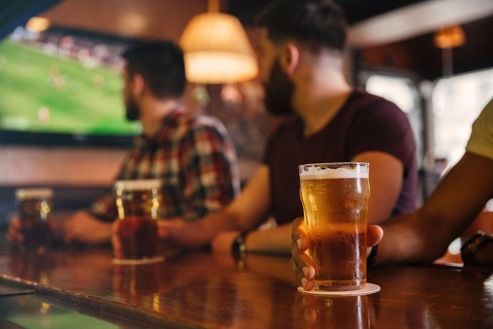 Beer glasses on bar with blurred men and football game in the background
