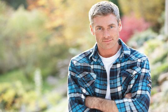 A handsome man with gray hair wearing a blue-and-white plaid shirt and his arms folded.