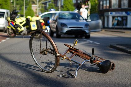 Bike lying on its side in the street with a car in background
