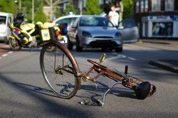 A bicycle lying on its side in the middle of the street