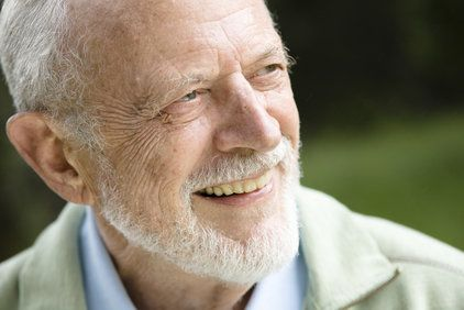 An elderly man with a clean-cut beard looks to his left while smiling.