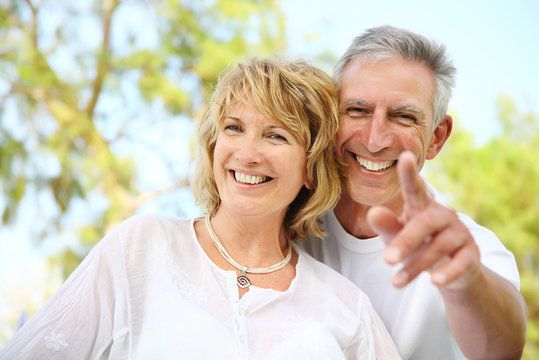Middle aged Caucasian couple smiling with man pointing interesting sight out to woman