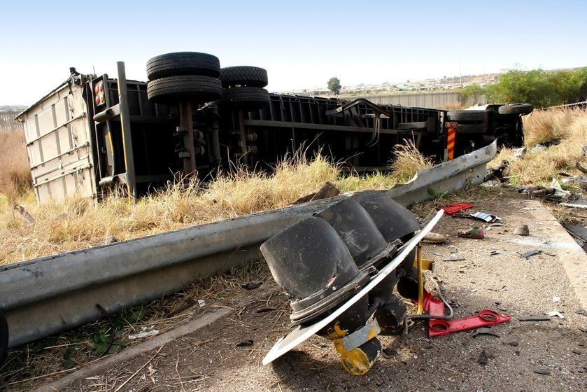 A commercial truck lying on its side behind a broken guard rail
