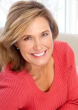 An attractive, middle-aged woman smiling, her eyes bright and alert after eyelid surgery
