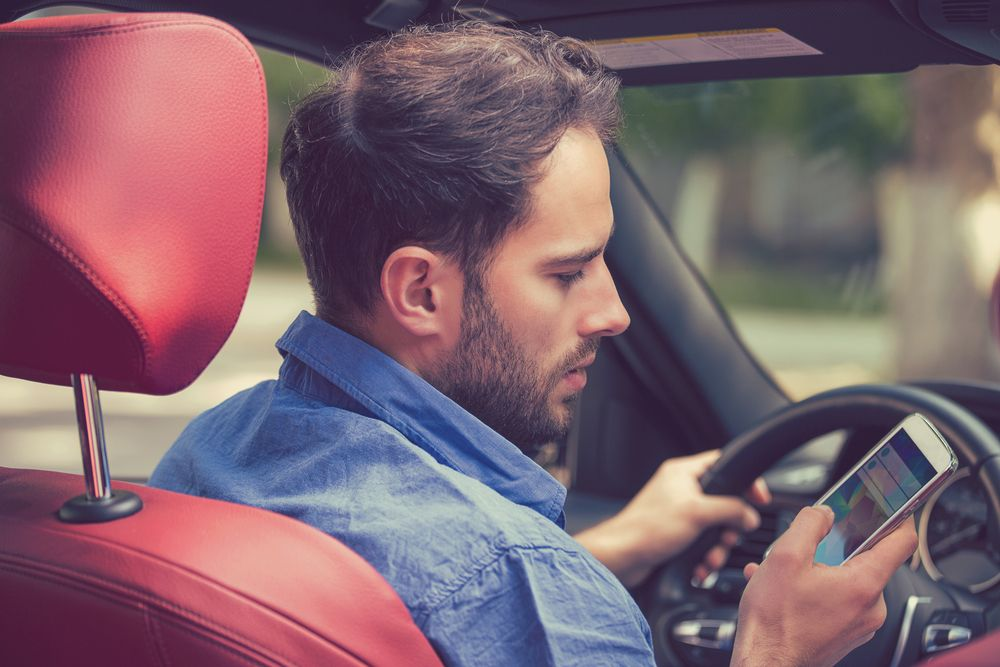 A man looks at his phone while at the wheel of a car.